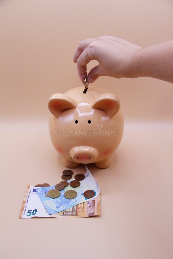 Räcka introduktion av ett mynt in i spargrisen med besparingar arkivfoton