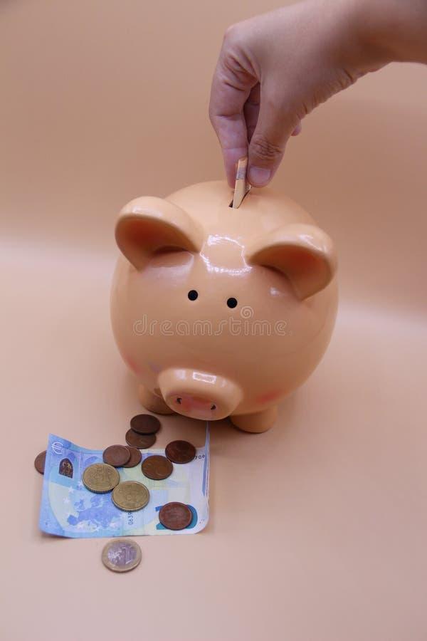 Räcka introduktion av ett mynt in i spargrisen med besparingar royaltyfria foton