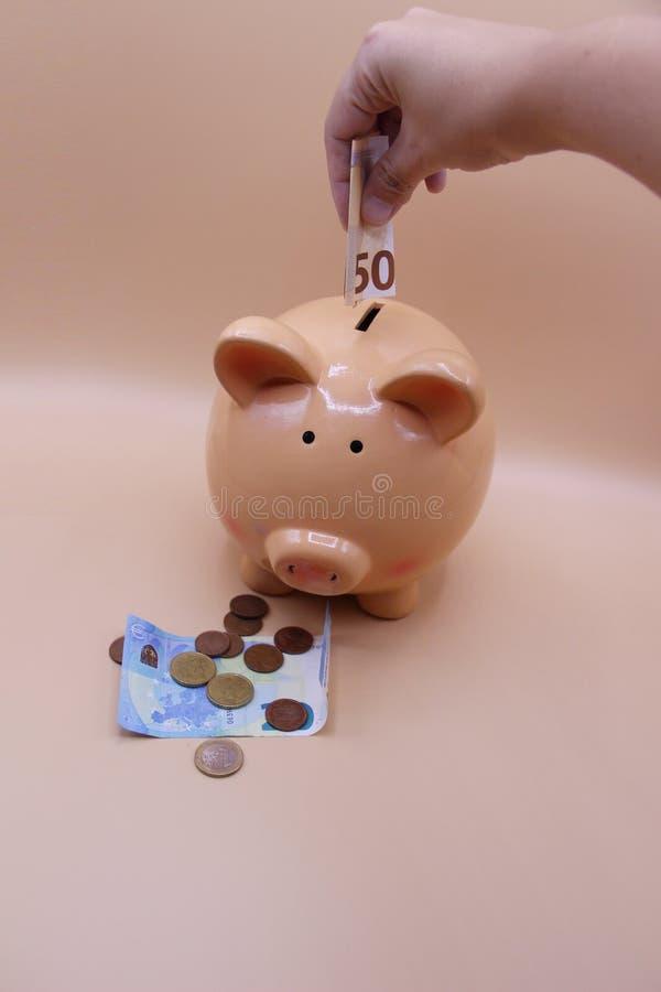 Räcka introduktion av ett mynt in i spargrisen med besparingar fotografering för bildbyråer