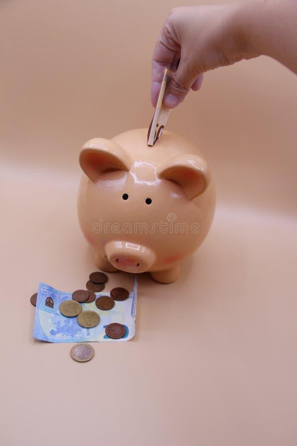 Räcka introduktion av ett mynt in i spargrisen med besparingar arkivbild