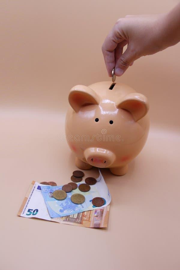 Räcka introduktion av ett mynt in i spargrisen med besparingar arkivfoto