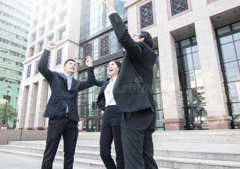 Räcka koordination av lagaffärsmannen på himmel i framdel av bankbuien arkivbild