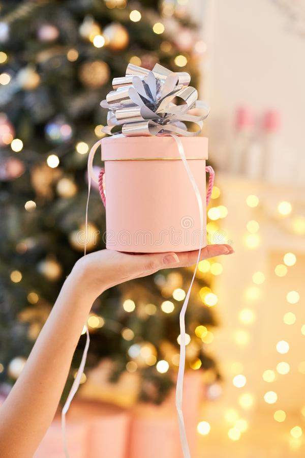 Räcka kvinnan den hållande rosa gåvaasken för nytt år på julbakgrund med utrymme royaltyfria foton
