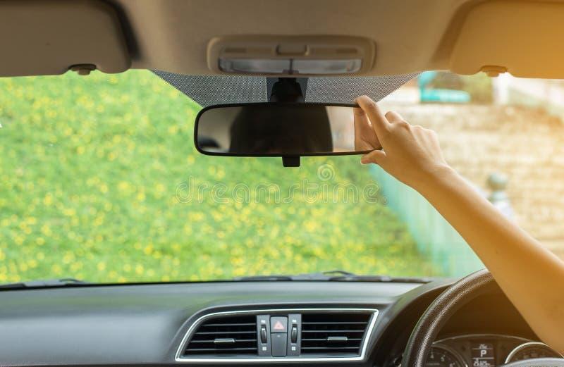 Räcka kvinnan som använder spegeln för den bakre sikten i det bil-, trans.- och medelsäkerhetsbegreppet fotografering för bildbyråer