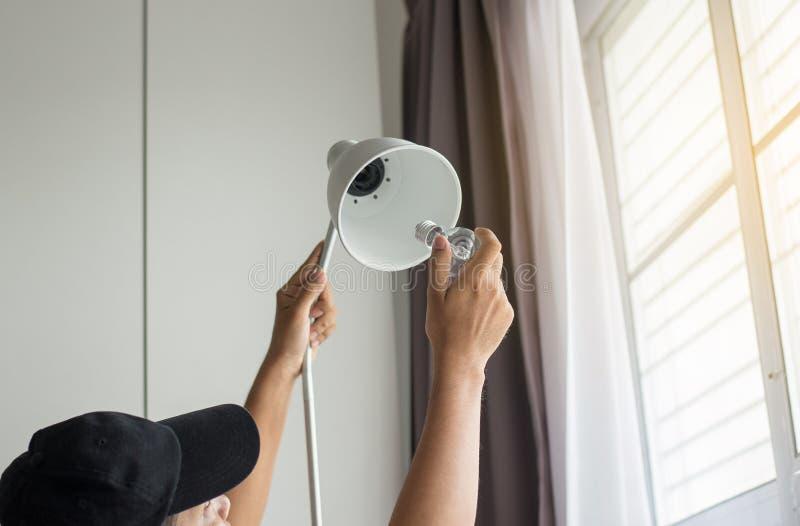 Räcka manmekanikern som ändrar med den nya LEDDE ljusa kulan för lampan, maktbesparingbegrepp royaltyfria foton