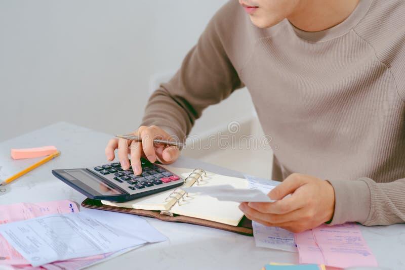 Räcka mannen som gör finanser och, beräkna på skrivbordet om kostnad hemma arkivfoto