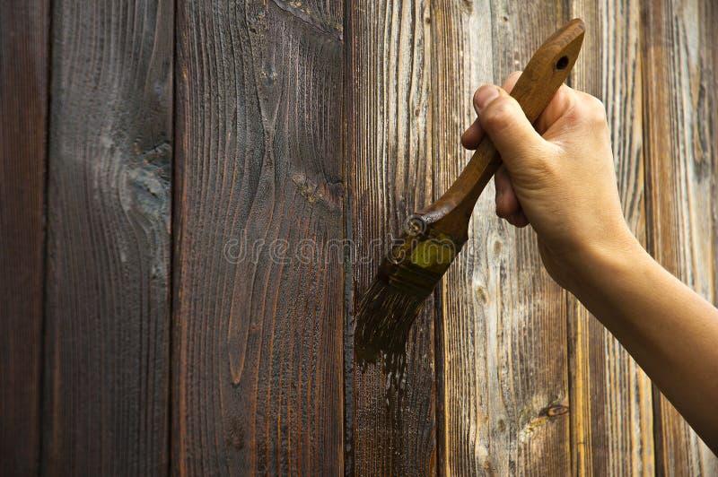 Räcka med paintbrushen på trä arkivbilder
