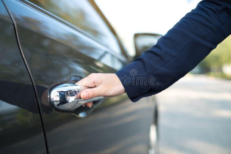 Räcka på handtaget Närbild av den kvinnliga handen som öppnar en bildörr arkivfoto