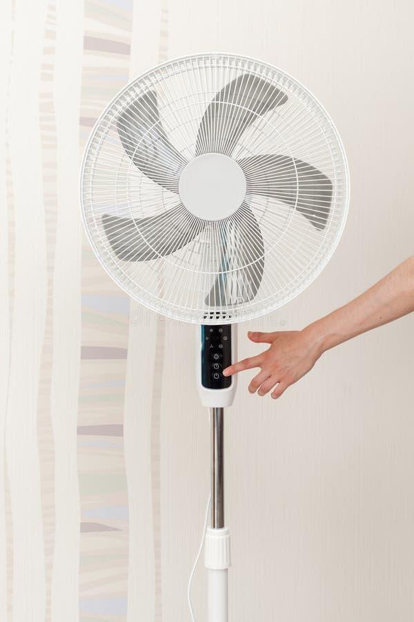 Räcka pressar knappen på kontrollbordet på det vita begreppet för den elektriska fanen: Spara energi, spara världen, spara pengar royaltyfri bild