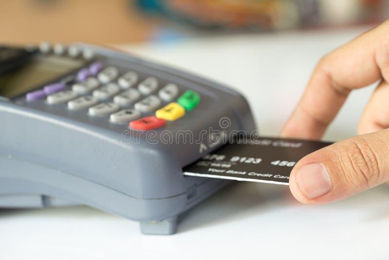 Räcka Pushkreditkorten in i en kreditkortmaskin arkivbilder