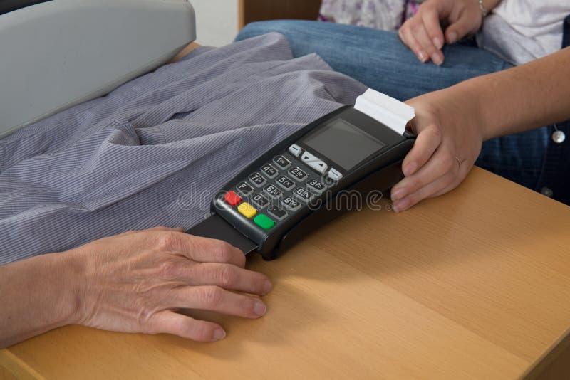 Räcka Pushkreditkorten in i en kreditkortmaskin arkivfoton