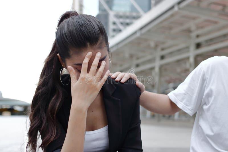 Räcka ` s av kollegan som tröstar den deprimerade ledsna asiatiska kvinnan med händer på framsidagråt arkivfoto