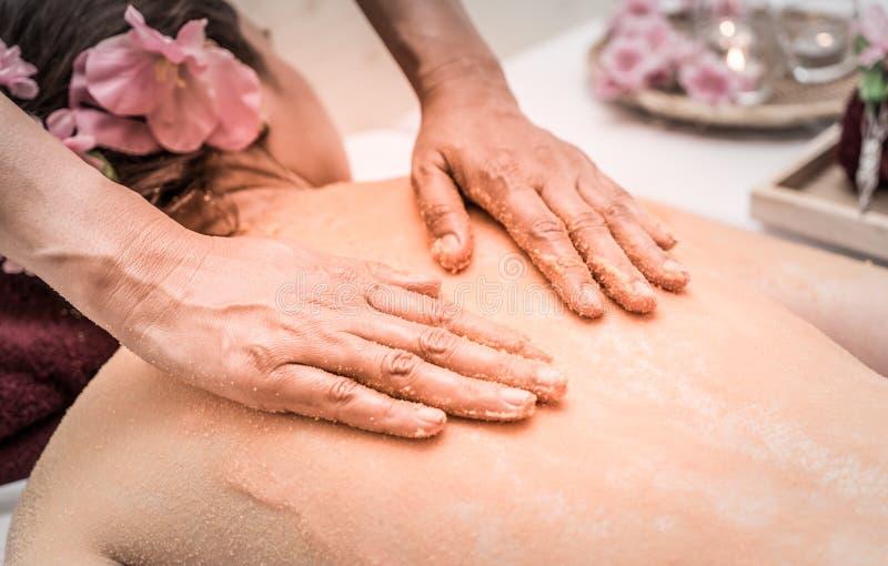 Räcka skurning salt på kvinnabaksida för Skincare arkivbild