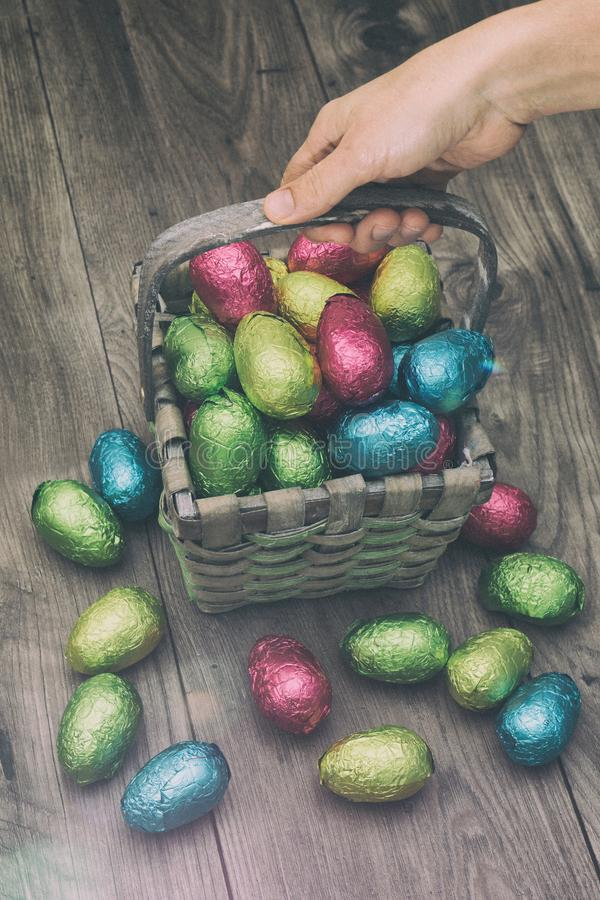 Räcka val upp av en sugrörkorg som fylls med påskchokladägg som slås in i färgrik tennfolie royaltyfria foton