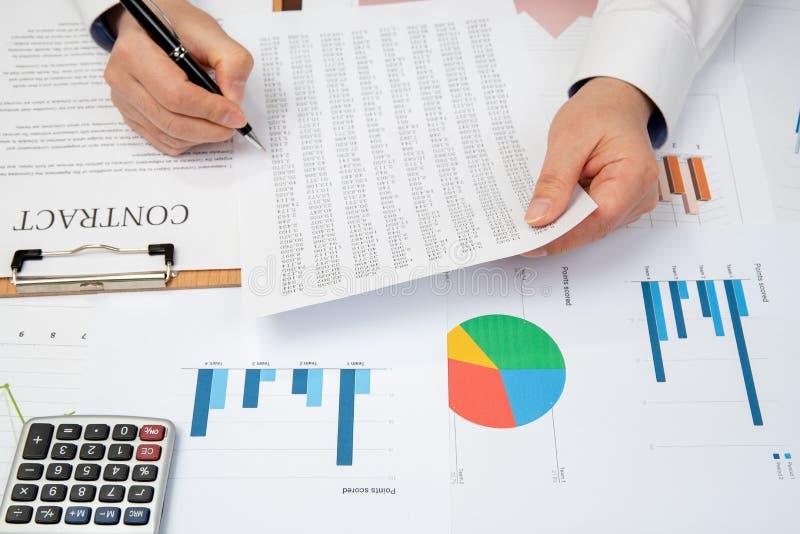 Räcker av affärsfolk som diskuterar ett nytt, projekterar Avtal, diagram och grafer på skrivbordet arkivbild