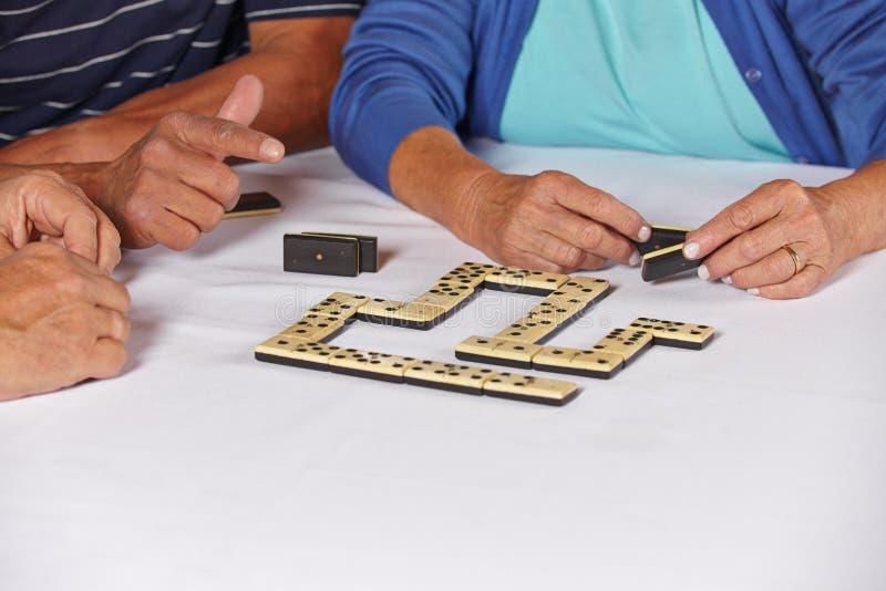 Räcker av pensionärer som leker domino arkivfoton