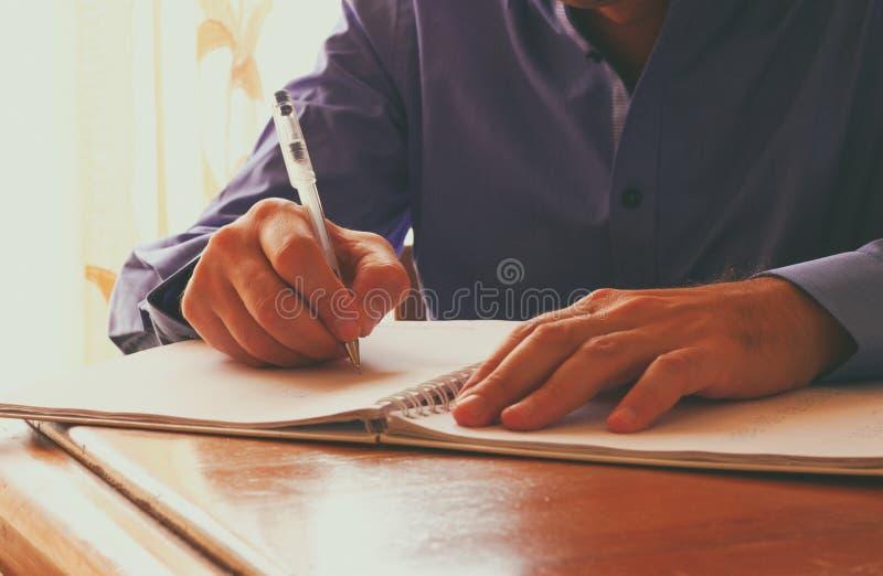 Räcker den övre bilden för slutet av mannen handstil på anteckningsboken Selektivt fokusera royaltyfri bild