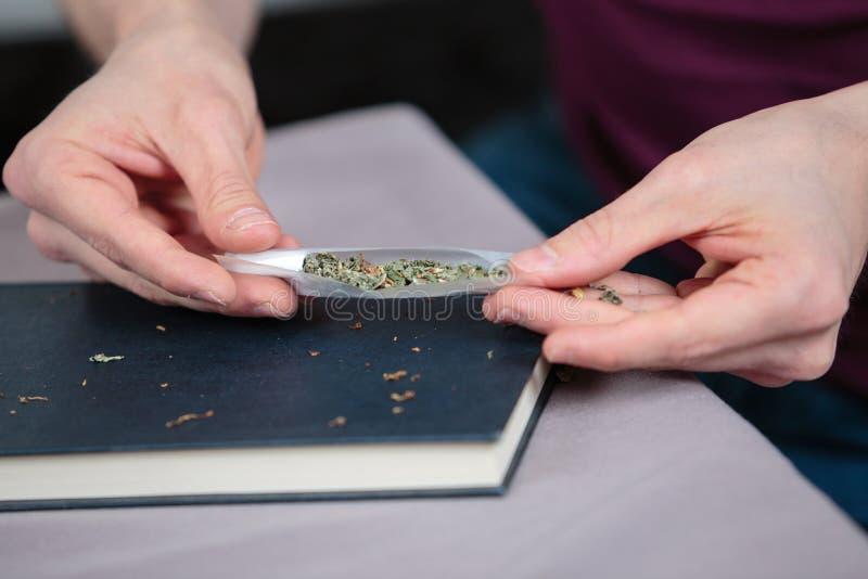 Räcker den preparaing cannabiscigaretten fotografering för bildbyråer