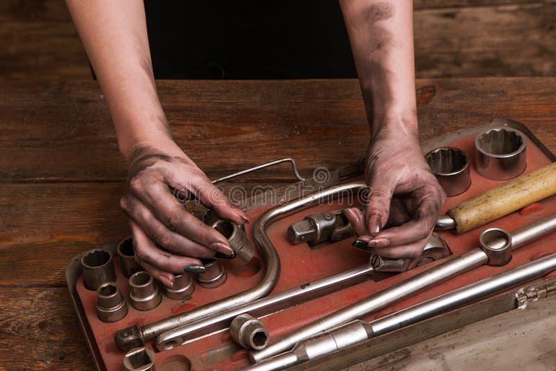 Räcker den smutsiga kvinnan för den kvinnliga mekanikern hjälpmedeluppsättningen royaltyfri fotografi