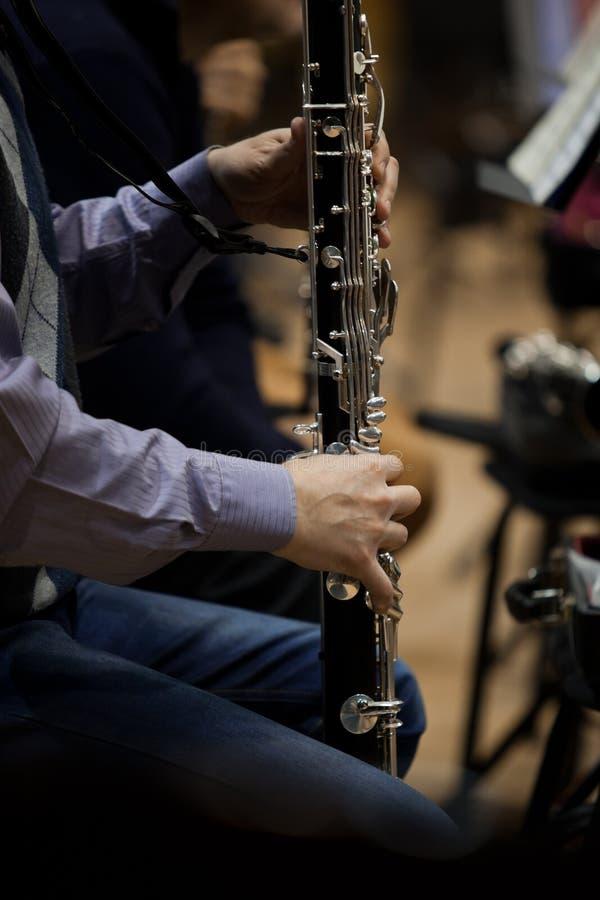 Räcker musikern som spelar den bas- klarinetten royaltyfri fotografi
