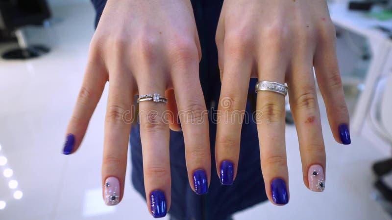 Räcker närbild manicure blue nailpolish En ung flicka visar henne manikyr på kameran, som gjordes för henne i a lager videofilmer
