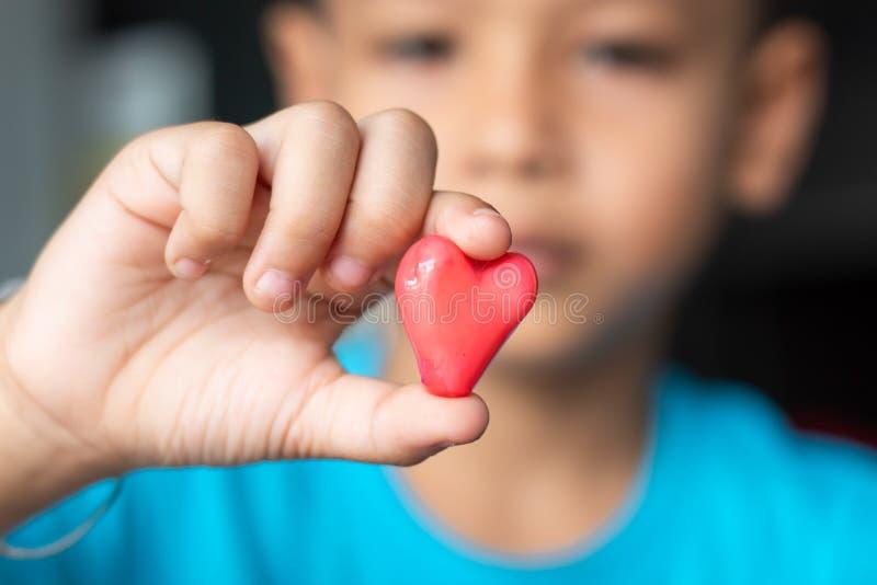 Räcker röd hjärta för godisen in en pojke royaltyfri bild