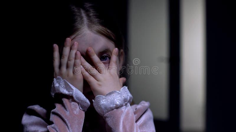 Rädd kvinnlig unge som piper genom fingrar vid kamera, fobi och ångest arkivbilder