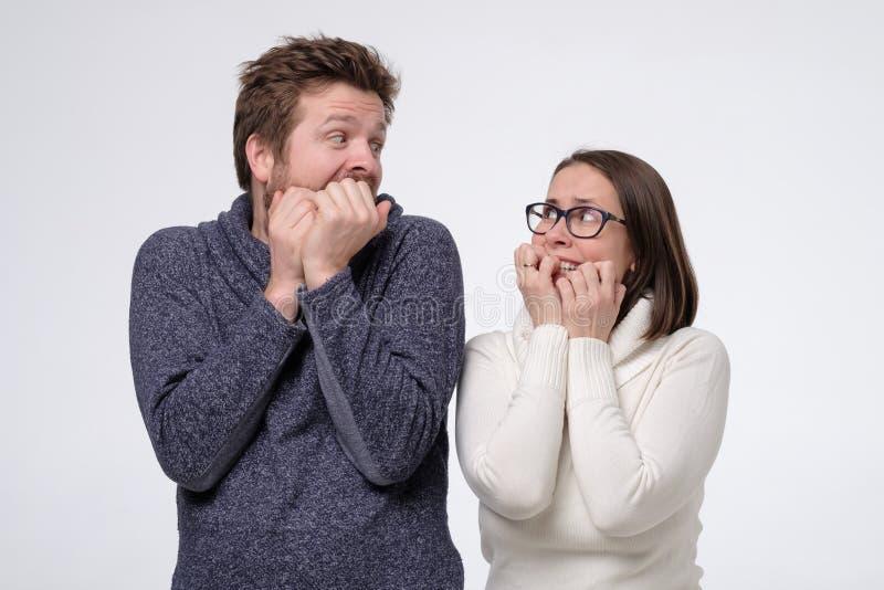 Rädd man och ett par som ser rädda på varandra fotografering för bildbyråer