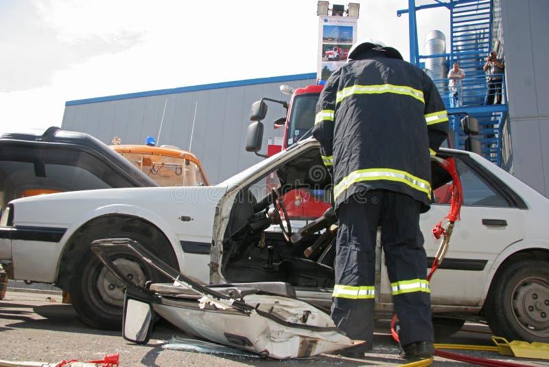Rädda brandmannen i handling för sparande folk från en bilkrasch framme av andra personer i Sofia, Bulgarien - September, 11, 200 fotografering för bildbyråer