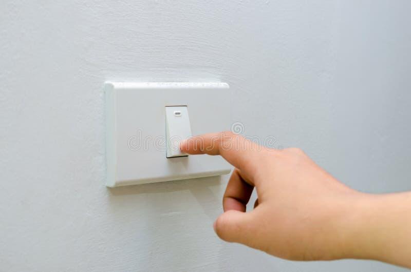 Räddningelektricitetsslutet av fingret vänder upp 'På/av' på den ljusa strömbrytaren kvinnahand med fingret på kopieringsutrymme  royaltyfri foto