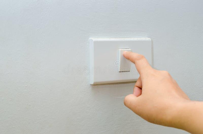 Räddningelektricitetsslutet av fingret vänder upp 'På/av' på den ljusa strömbrytaren kvinnahand med fingret på kopieringsutrymme  royaltyfri bild