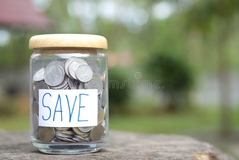 Räddningpengarbegrepp med myntet i flaska på utrymme för bokehbakgrundskopia royaltyfri fotografi