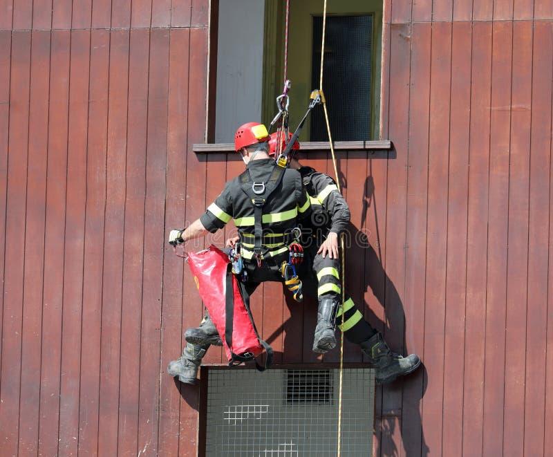 räddningsaktionövningar av en brandman och en person som simulerar royaltyfria foton