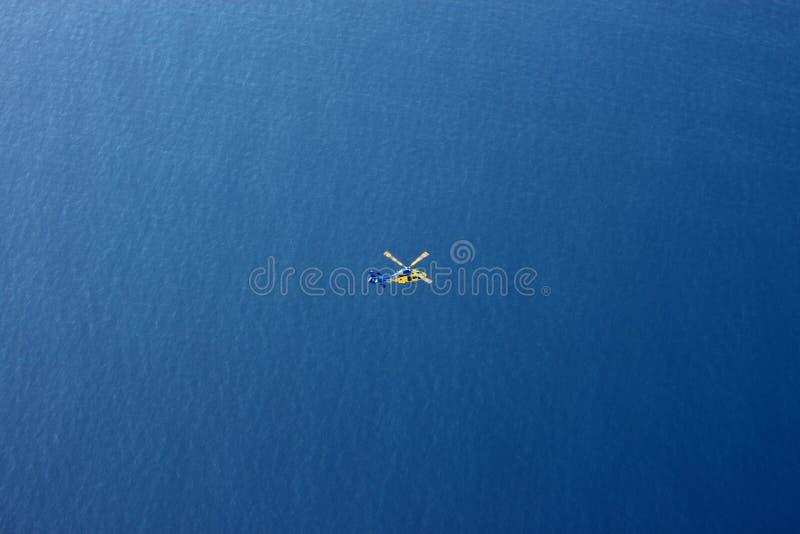 Räddningsaktionhelikopter i flyg- sikt för vidsträckt hav arkivbild