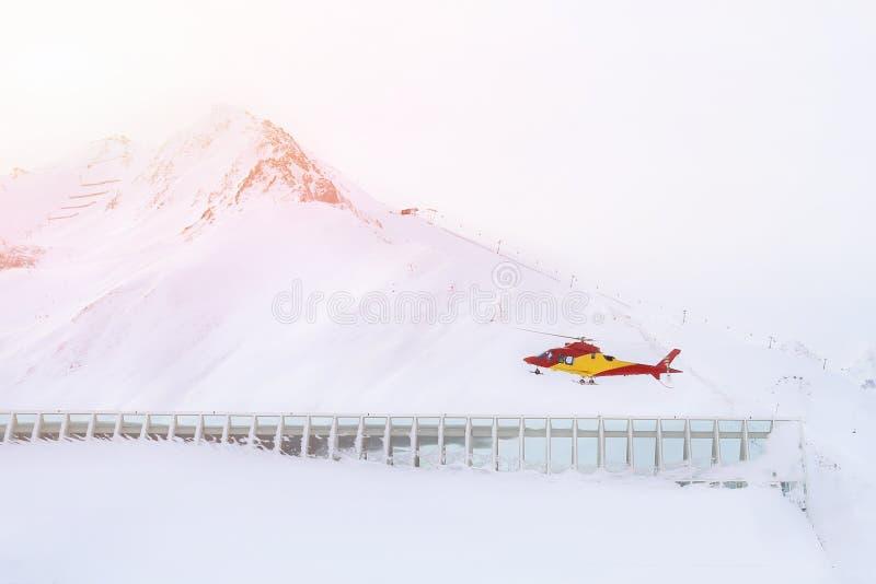 Räddningsaktionhelikopterlandning på lutningar på skidar semesterorten i alpina berg Nöd- olycksservice royaltyfri foto
