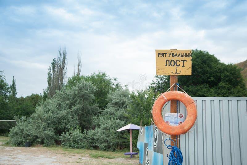 Räddningsaktionstation på stranden på solig dag Tecken på kusten Text i ukrainare: preserver för liv för räddningsaktionstolpe rö royaltyfria bilder