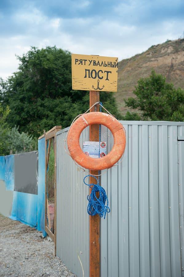 Räddningsaktionstation på stranden på solig dag Tecken på kusten Text i ukrainare: preserver för liv för räddningsaktionstolpe rö royaltyfri fotografi