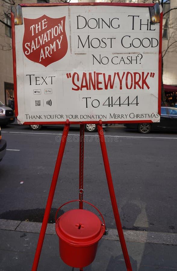 Räddningsarméns skylt och röda vattenkokare för samlingar i mellersta Manhattan royaltyfri bild