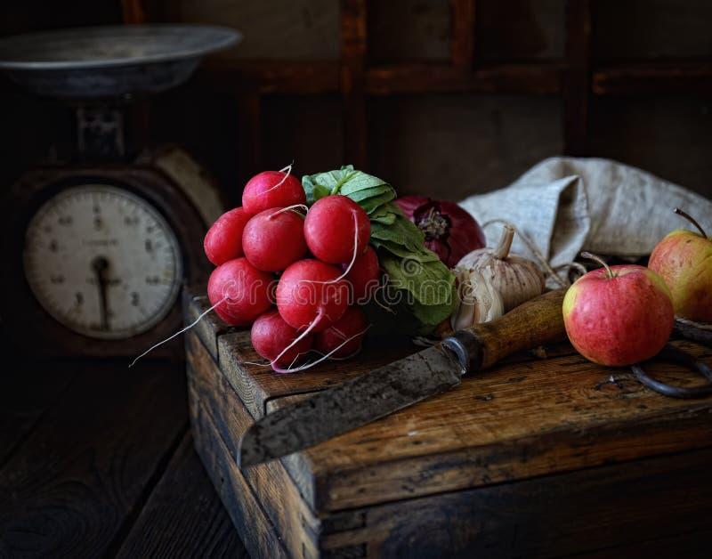 Rädisagrupp, kniv, äpplen på en träask, tappningvåg på en mörk bakgrund fotografering för bildbyråer