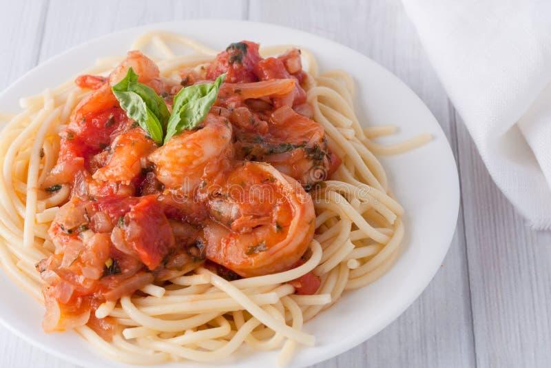 Räka i vintomatsås över spagettipasta arkivfoto