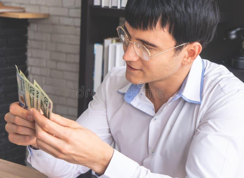 Räkna för affärsman av mer pengar som direktanslutet arbetar arkivbilder