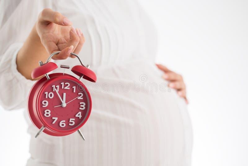Räkna timmar som förväntar barnfödelse Isolerat på vitbakgrund Pregna royaltyfri bild