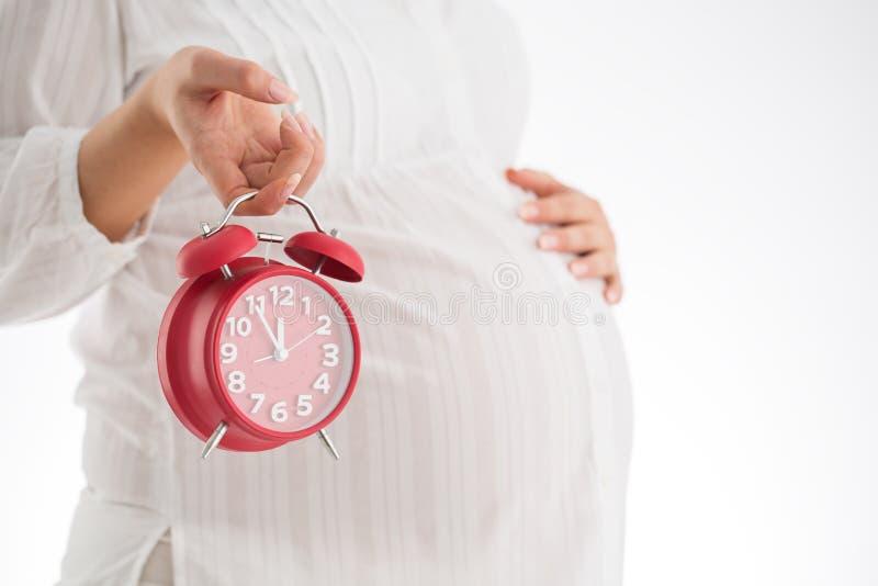 Räkna timmar som förväntar barnfödelse Isolerat på vitbakgrund Pregna royaltyfria bilder