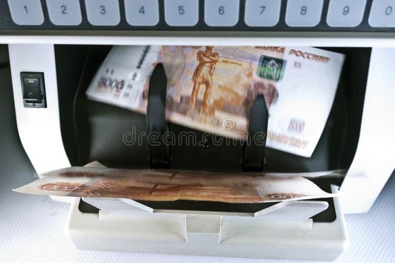 Räknarapparaten för elektroniska pengar räknar de ryska 5/00 rubelsedlarna, suddig, rörelsens effekt arkivfoto