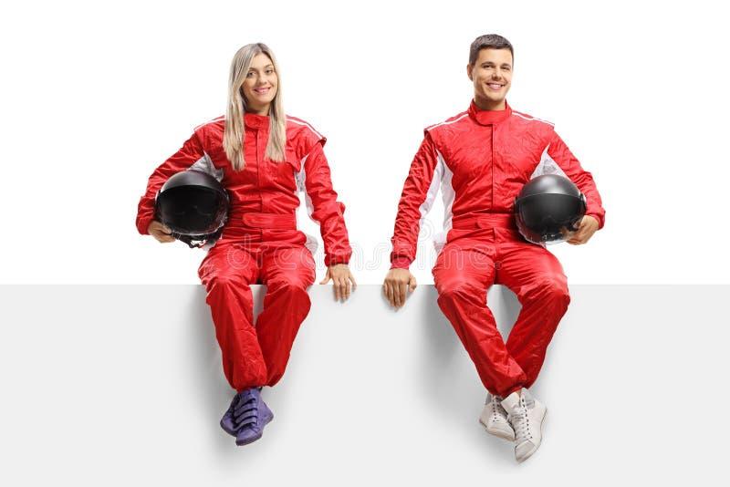 Räknare för manliga och kvinnliga bilar som sitter på en panel i röda uniformer arkivbild