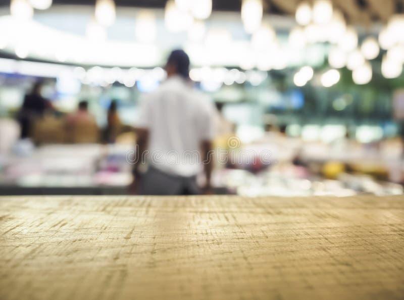 Räknaren för tabellöverkanten med suddigt folk shoppar inre backgroud arkivbild