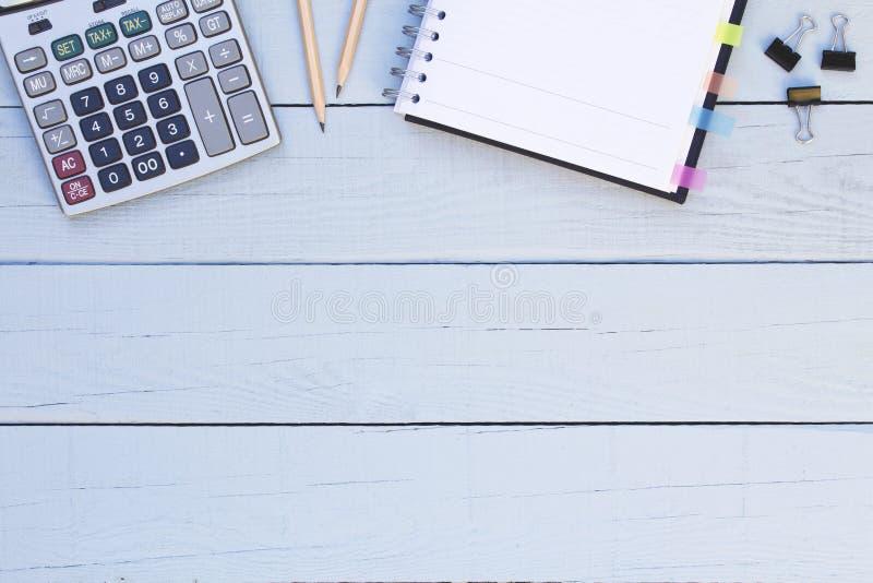 Räknemaskin, anteckningsbok och blyertspennor på träblå bakgrund royaltyfria foton