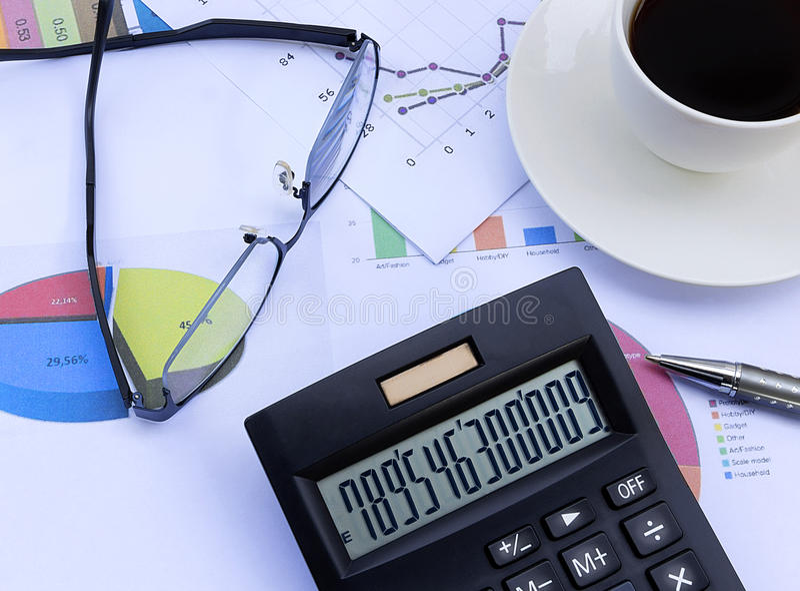 Räknemaskin, exponeringsglas, penna, kaffekopp och finansiellt diagram, busine arkivbild