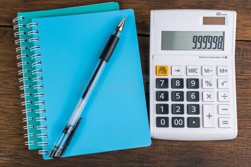 Räknemaskin med anteckningsboken och pennan arkivfoton