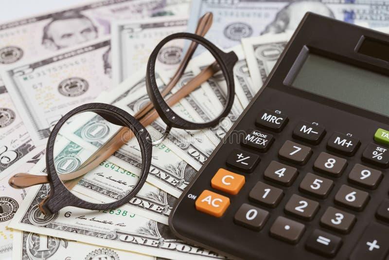 Räknemaskin med glasögon på US dollarsedelpengar genom att använda som företagsbudget, investering, bankrörelsen eller finansiell royaltyfri foto